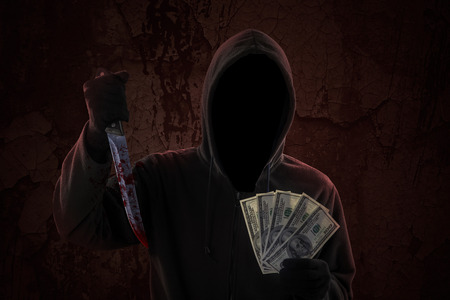 Mysterious man wearing hoodie while holding bloody knife and money cash photo