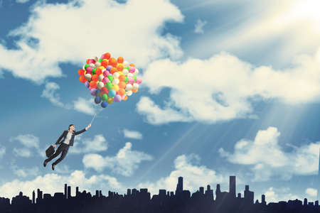 realize: Businesswoman flying with balloons over cityscape to get success Stock Photo