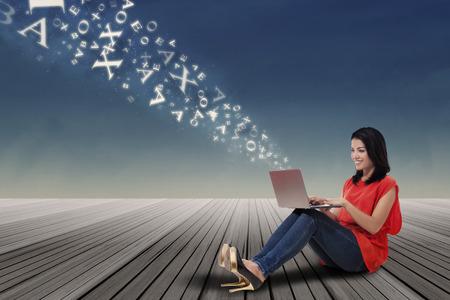 fille indienne: Jeune femme d�contract�e assis sur le sol tout en utilisant un ordinateur portable pour envoyer des informations vers le ciel