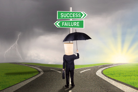 solutions freeway: Entrepreneur with a carton head and holds an umbrella, standing on the road while looking at two signpost to success or failure