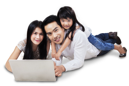 Happy family lying down on the floor while surfing on internet online with laptop, isolated over white photo