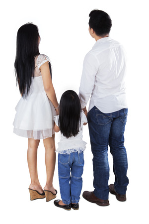 holding back: Full length of family standing in the studio while looking back, isolated over white background Stock Photo