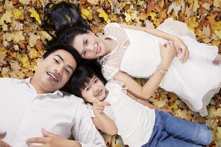 asian mother and daughter: Unique perspective of lovely family lying down on the autumn leaves while looking at the camera