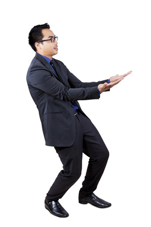 Portrait of young businessperson carrying something with his hands, shot in the studio photo