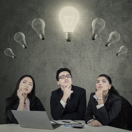 indonesian woman: Portrait of businessteam with thinking expression while looking at lightbulb