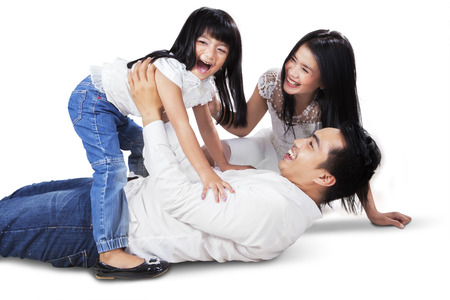 girl bonding: Joyful asian family laughing and playing together on the floor, shot in the studio isolated on white