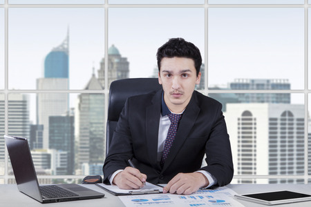 Young businessperson writing on the clipboard while looking at the camera in the office room photo
