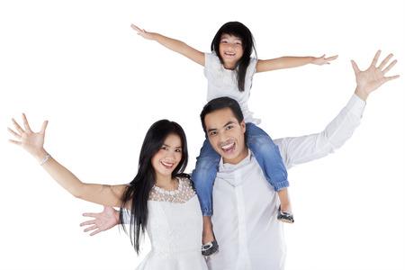 gente celebrando: Retrato de familia feliz elevar las manos en alto, mientras que mirando y sonriendo a la cámara, aislado en blanco Foto de archivo