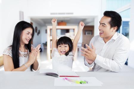 Aufgeregt kleinen Mädchen ihr Glück nach Beendigung ihrer Schularbeiten und bekommen schätzen ausdrücken
