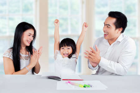 Happy little girl finishing her homework and get applause from her parents at home photo