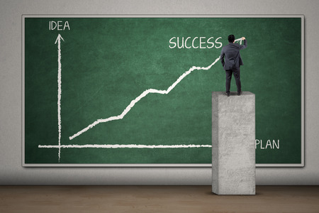 sales strategy: Back view of businessman drawing a plan statistics to get success