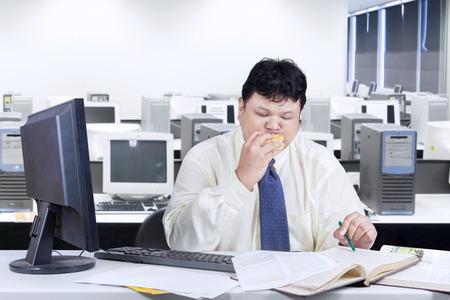 malos habitos: Obeso empresario trabajando en la mesa mientras muerde una hamburguesa, un disparo en la oficina