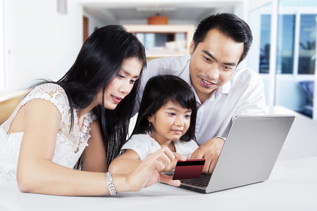 Modern family using a laptop computer and credit card to online shopping at home photo
