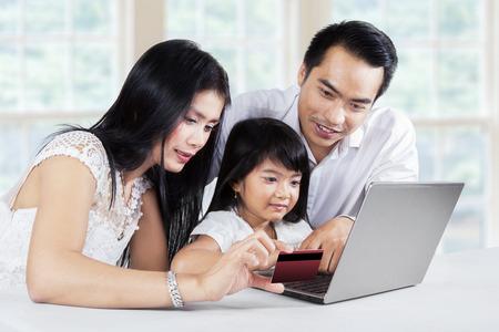 ni�os de compras: Familia feliz que hace el pago en l�nea mediante el uso de una tarjeta de cr�dito y la computadora port�til en casa