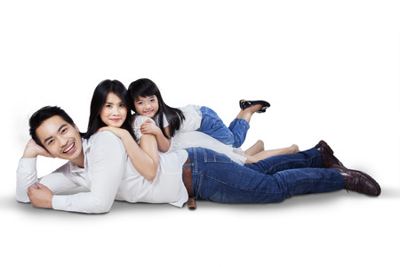 staring at the camera man: Happy family lying down on the floor while smiling at the camera, isolated over white background