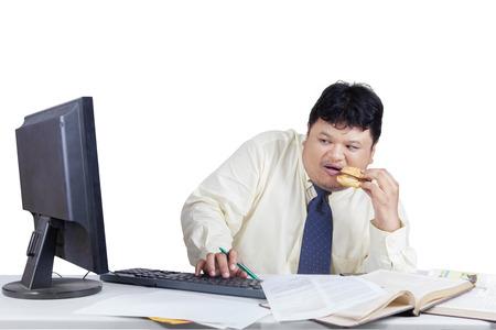 monitor de computadora: Empresario de trabajo con el ordenador, mientras que comer hamburguesa y mira asustado cuando se mira el monitor