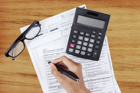 high cost of healthcare: Hand writes the personal information on the health insurance claim form Stock Photo