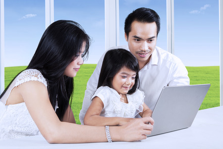 Little girl using a laptop computer on the table with her parents, shot at home photo