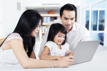 Cute little girl using laptop computer on the table with her parents, shot at thome photo