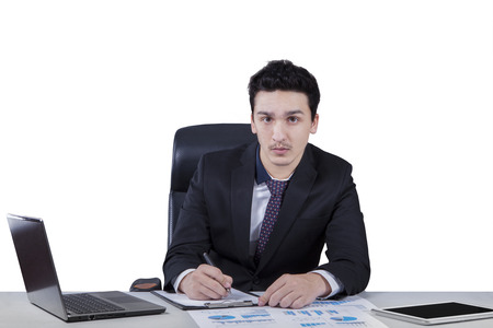Young caucasian writes on paperwork while looking at the camera, isolated over white photo
