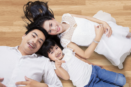 Unique perspective of happy family lying down on the wooden floor while looking at the camera