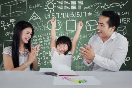 Cheerful little girl get appreciation and applause from her parents after studying photo
