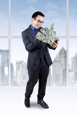 Joyful businessman standing in the office while looking at money dollar coming out from his cellphone