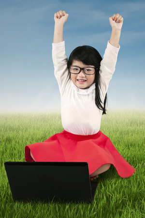 field study: Cute little girl raise hands to celebrate her achievement while sitting on the meadow with laptop