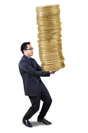 Portrait of young entrepreneur carrying a pile of coins, isolated on white background photo