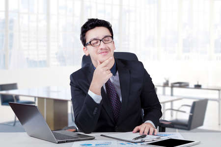 Young caucasian businessman smiling happy while working and imagine something in the workplace photo