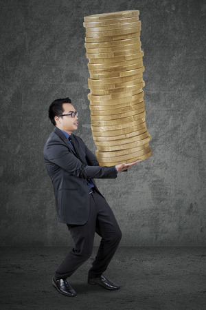 taxation: Young male manager carrying a stack of golden coins, symbolizing high profit