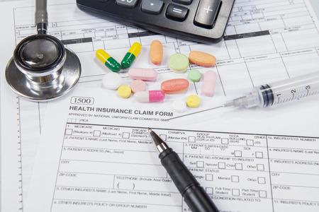 registros contables: Primer de la forma de seguro de salud con drogas, jeringuilla, bolígrafo, calculadora y un estetoscopio Foto de archivo