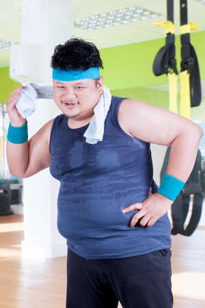 endeavor: Overweight person smiling at the camera while wiping his sweat with a towel at fitness center