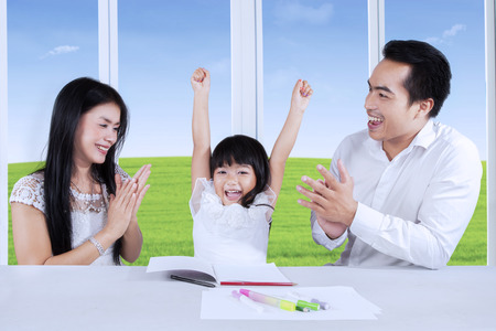 Happy parents clapping hands to appreciate their daughter after finishing homework photo