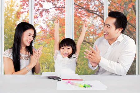 rewards: Two parents giving applause to their daughter after finishing her homework Stock Photo