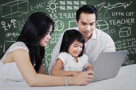 Two parents help their daughter to study by using a laptop computer on the table photo