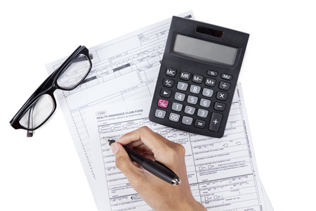 high cost of healthcare: Closeup of hand writes on the medical insurance form with calculator and glasses