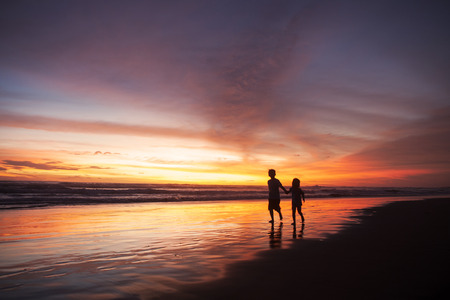 Silhouette of happy children playing on the beach while holding hands at sunset time photo