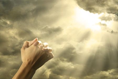 worship praise: Closeup of prayer raised hands on the sky with bright rays from the cloud Stock Photo