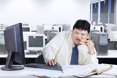 overweight man: Male worker looks scared when looking at a monitor in the office while eating a burger Stock Photo