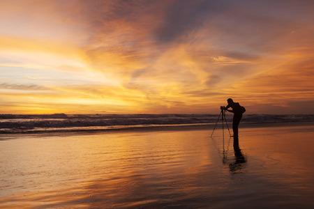 personas tomando agua: Fotógrafo de sexo masculino toma foto con la cámara réflex digital en la playa de la puesta del sol