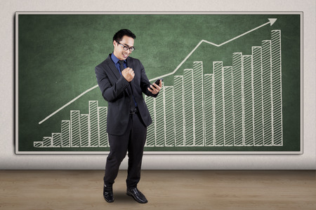 up growth: Happy businessman reading a good news on cellphone while standing in front of business graph