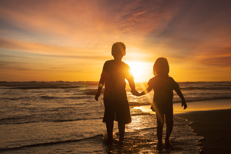 Silhouette of two children walking on the beach while holding hands with sunset background on the back Foto de archivo
