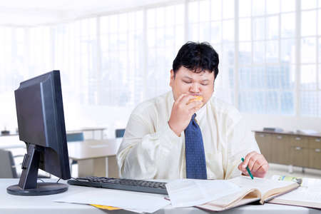 obese man: Male entrepreneur sitting in the office while looking at the book and biting a burger