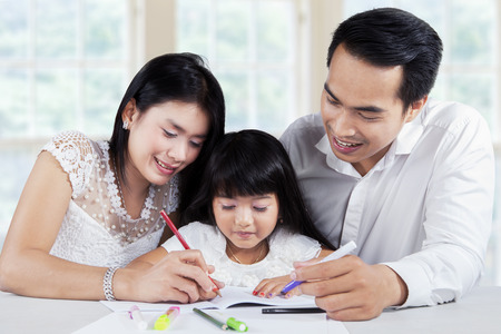 schoolwork: Two parents help their daughter doing schoolwork on the table at home