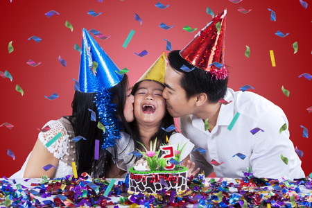 fiesta familiar: Familia asiática joven llevaba gorra de cumpleaños y besando al niño en la fiesta de cumpleaños