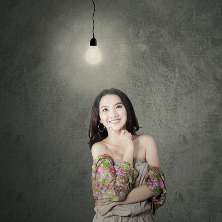 Lovely modern teenag girl smiling happy while thinking an idea under a bright lamp photo