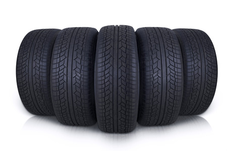 tire repair shop: Closeup of five vehicle tires with black color in the studio, isolated on white background