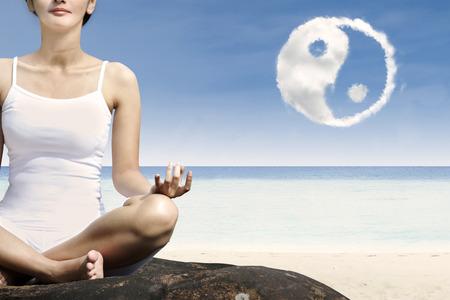 ying yang: Close-up woman exercise yoga at beach with ying yang cloud