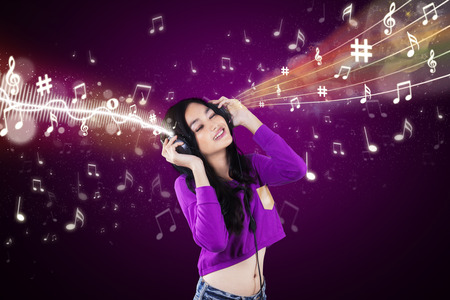 dj music: Beautiful teenage girl listening music with earphones, shot against purple background